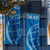 Flags with DAAD logo in front of the outer facade of the headquarters in Bonn.